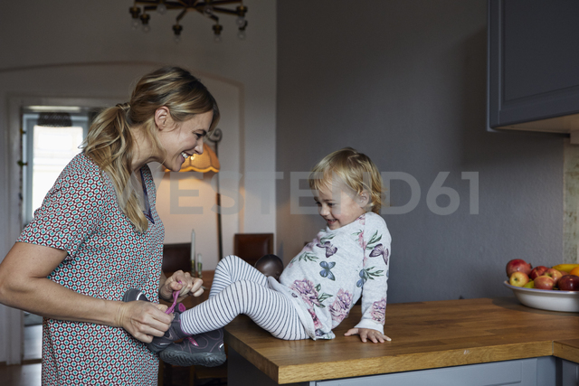 Mother tying shoe of her little daughter in the kitchen - RBF06187 - Rainer Berg/Westend61