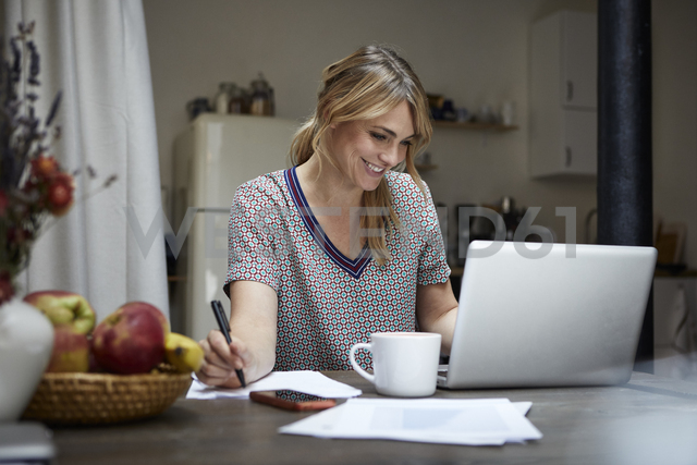 Portrait of laughing woman working on laptop at home - RBF06190 - Rainer Berg/Westend61