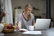 Portrait of laughing woman working on laptop at home - RBF06190
