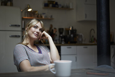 Portrait of daydreaming woman  sitting at table in the kitchen - RBF06193