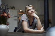 Portrait of smiling woman sitting at table in the kitchen thinking - RBF06196