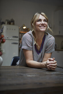 Portrait of happy woman leaning on kitchen table - RBF06199