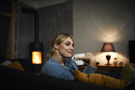 Portrait of happy woman with cup of tea relaxing on couch at home in the evening - RBF06202
