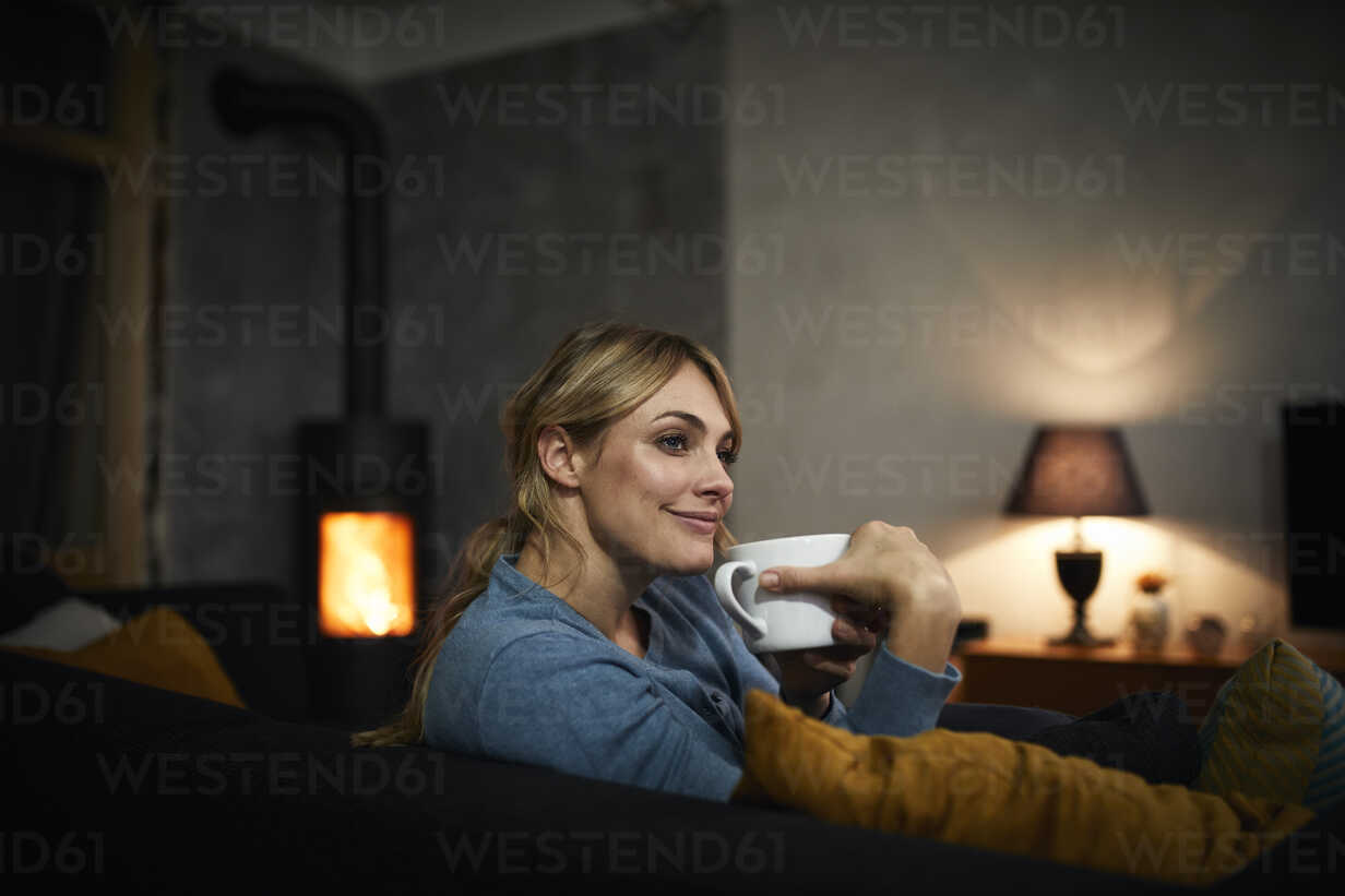 Portrait of happy woman with cup of tea relaxing on couch at home in the evening - RBF06202 - Rainer Berg/Westend61