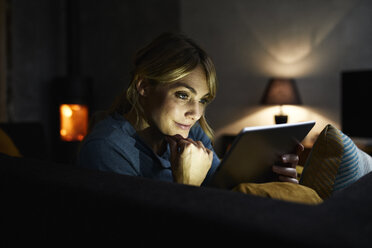 Portrait of smiling woman using tablet on the couch at home in the evening - RBF06205