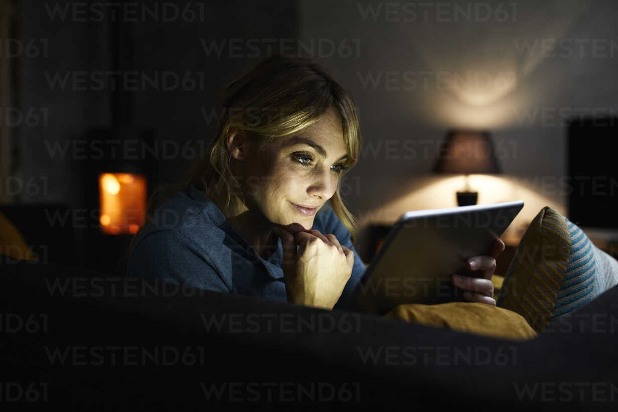 Portrait of smiling woman using tablet on the couch at home in the evening - RBF06205 - Rainer Berg/Westend61