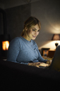 Portrait of smiling woman using laptop at home in the evening - RBF06208
