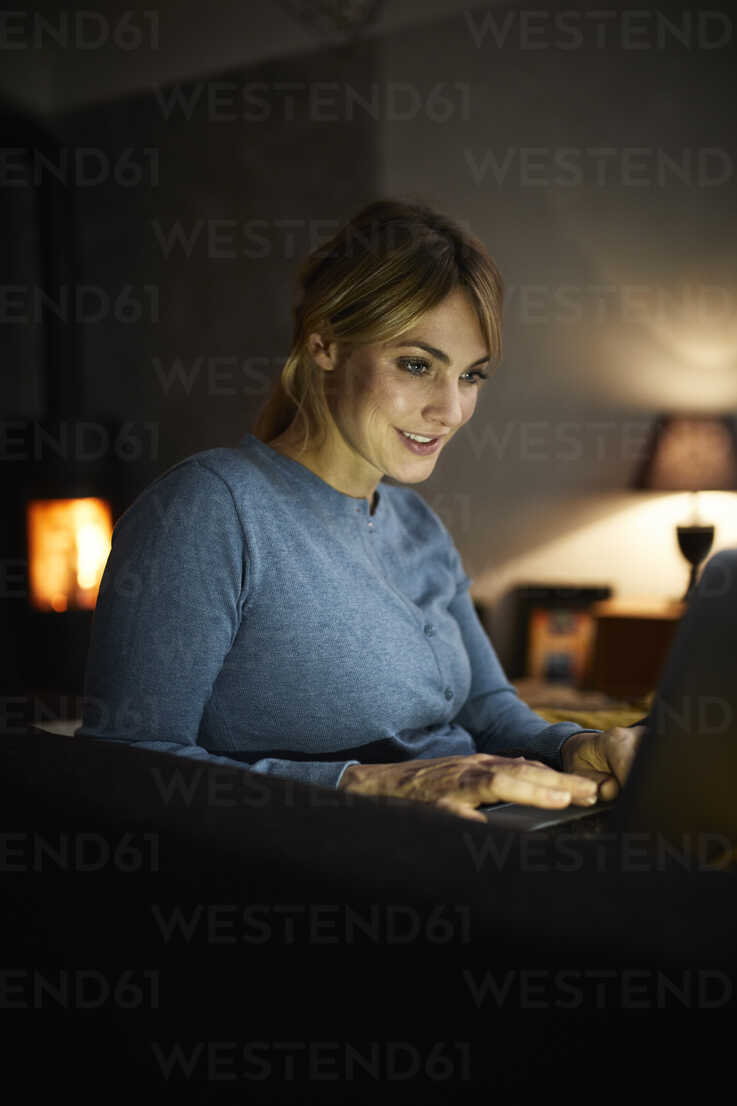 Portrait of smiling woman using laptop at home in the evening - RBF06208 - Rainer Berg/Westend61