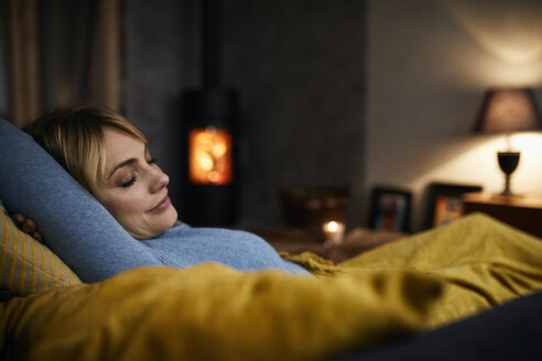 Portrait of smiling woman relaxing on couch at home in the evening - RBF06211