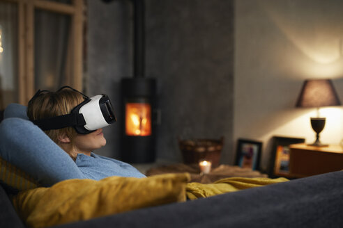 Woman lying on couch at home in the evening using Virtual Reality Glasses - RBF06214
