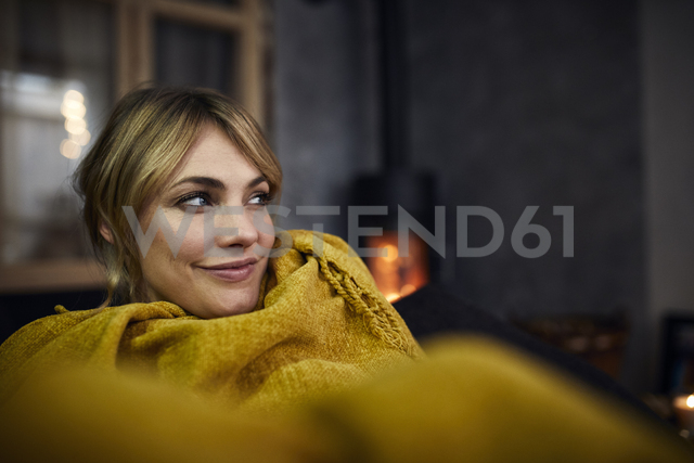 Portrait of smiling woman relaxing on couch at home in the evening - RBF06217