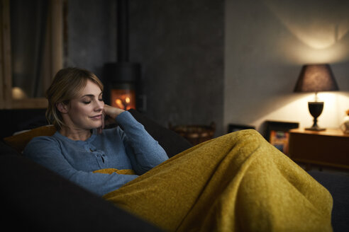 Portrait of smiling woman relaxing on couch at home in the evening - RBF06220