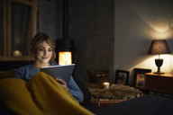 Portrait of smiling woman with tablet relaxing on couch in the evening - RBF06223