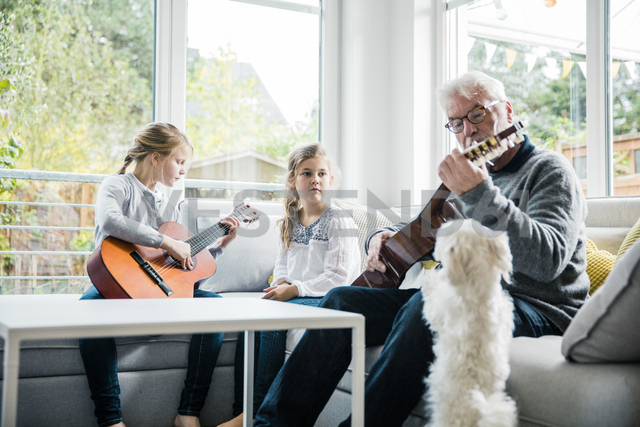 Two girls and grandfather on sofa playing guitar with dog watching - MOEF00518 - Robijn Page/Westend61