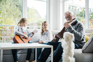 Two girls and grandfather on sofa playing guitar with dog watching - MOEF00518