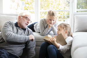Two girls and grandfather reading book in living room - MOEF00524