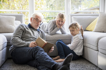 Two girls and grandfather reading book in living room - MOEF00527
