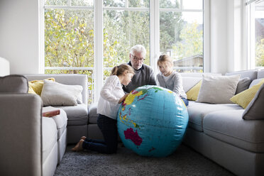 Two girls and grandfather with globe in living room - MOEF00530