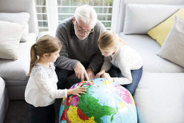Two girls and grandfather with globe in living room - MOEF00533