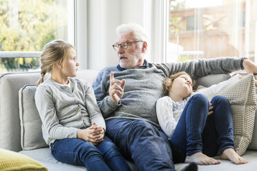 Grandfather talking to two girls on sofa in living room - MOEF00536