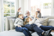 Two happy girls and grandfather on sofa taking a selfie - MOEF00539