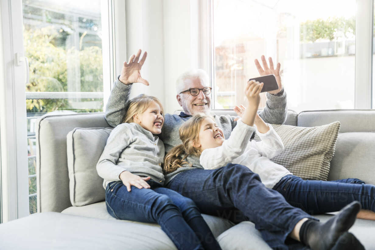 Two happy girls and grandfather on sofa taking a selfie - MOEF00539 - Robijn Page/Westend61