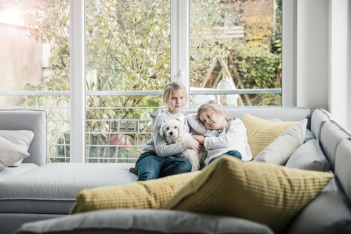 Portrait of two girls with dog on couch in living room - MOEF00545