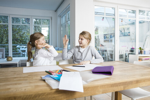 Two girls doing homework at table together high fiving - MOEF00548