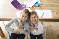 Portrait of two happy girls embracing at table together - MOEF00551