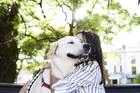 Young woman hugging her dog - IGGF00318