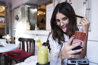 Young woman sitting in a coffee shop taking selfie with smartphone - IGGF00330