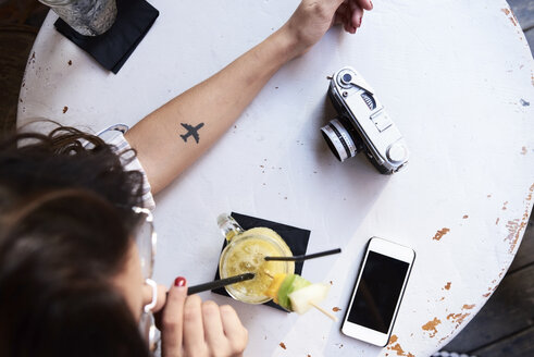 Young woman with airplane tattoo on her forearm sitting in a coffee shop drinking pineapple smoothie - IGGF00333