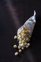 Paper bag of popcorn on rusty background - CSF28653