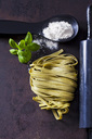Green Tagliatelle, spoon of flour, basil leaves and rolling pin on rusty ground - CSF28656