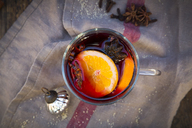 Glass of mulled wine with orange slices, cinnamon sticks, star anise and cloves at Christmas time - LVF06549