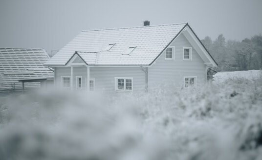 Grass and snow, frame house in the background - KMKF00095