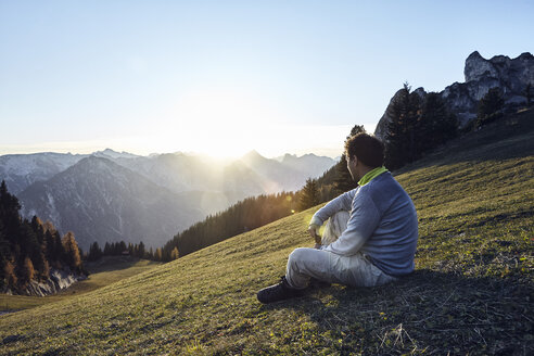 Austria, Tyrol, Rofan Mountains, hiker sitting on meadow at sunset - RBF06224