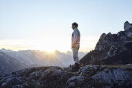 Austria, Tyrol, Rofan Mountains, hiker standing on rocks at sunset - RBF06227