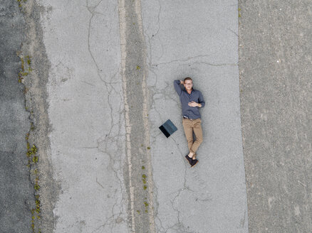 Young businessman with laptop relaxing in solitude, quadcopter view - KNSF03240