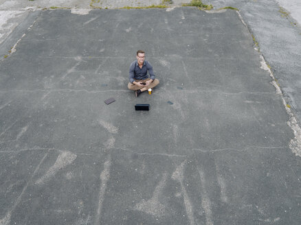 Young businessman with coffee to go and several mobile devices sitting on tarmac - KNSF03243