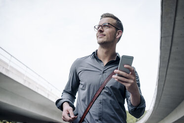 Portrait of smiling young businessman with smartphone - KNSF03255