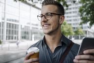 Portrait of laughing young businessman with coffee to go and smartphone - KNSF03258