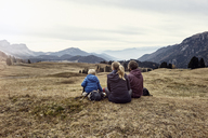 Italy, South Tyrol, Geissler group, family hiking, sitting on meadow - RBF06237