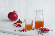 Glass and bottle of pomegranate juice and whole pomegranate and pomegranate seed - ASF06136