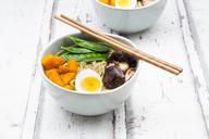 Ramen with noodles, egg, hokkaido pumpkin, mung sprout, shitake mushroom in bowl, chopsticks - LVF06550