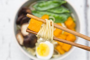 Ramen with noodles, egg, hokkaido pumpkin, shitake mushroom in bowl, chopsticks with noodles - LVF06553