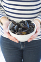 Woman holding bowl with fresh blue mussels - LVF06556