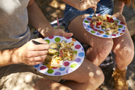 Young couple during picknick, plates with noodles - SRYF00585