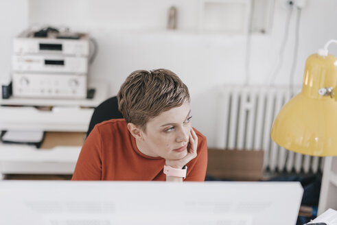 Woman at desk in office thinking - KNSF03272