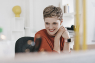 Portrait of smiling woman at desk in office - KNSF03275